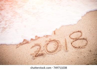 inscription 2017 and 2018 on a beach sand