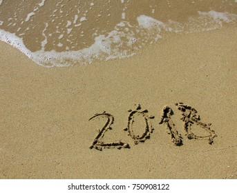 inscription 2018 on the sand