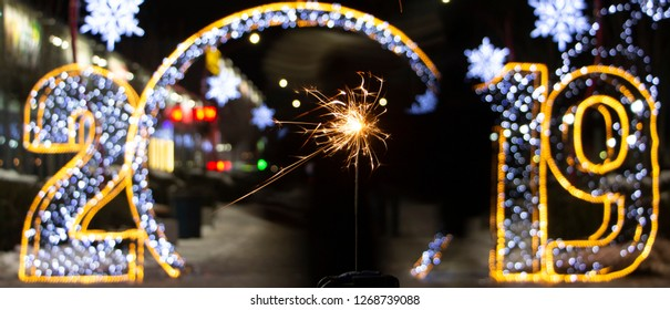 The inscription 2019 in Rasfokus, sparkler in the foreground, the concept of the new year