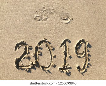 inscription 2019 in the sand of the beach, the trace of bare foot