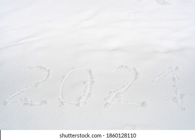 """The inscription """"2021"""" is written at the pure snow. New year natural snow background."""