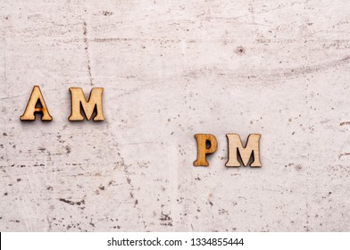Inscription a.m. ante meridiem, in the morning, p.m. post meridiem, in the afternoon abbreviation in wooden letters on a light background.
