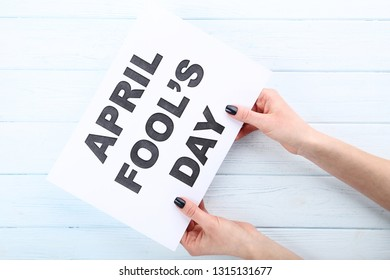 Inscription April Fool's Day on paper in female hands