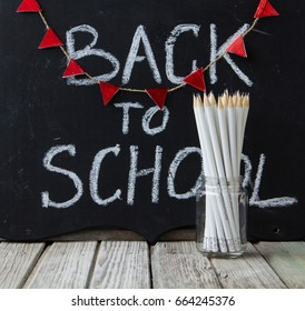 Inscription back to school on blackboard and pencils