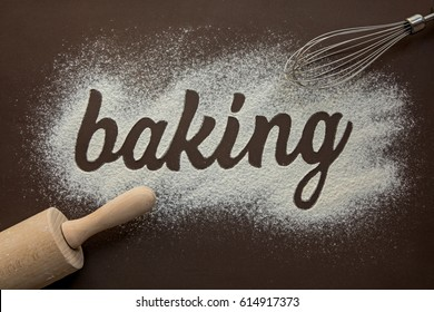 Inscription – baking, written by flour. On the brown background.
