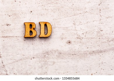 Inscription BD BDAY birthday abbreviation in wooden letters on a light background.
