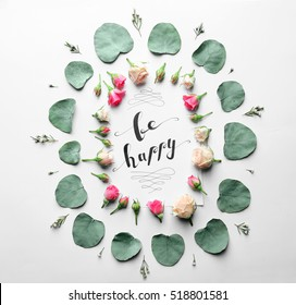 "Inscription ""BE HAPPY"" written on paper with flowers and leaves on white background"