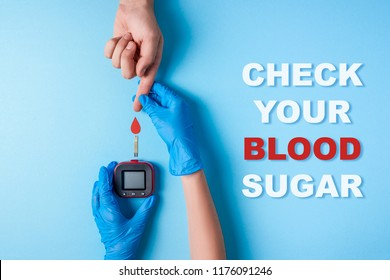 inscription check your blood sugar and Nurse making a blood test. . Man's hand with red blood drop with Blood glucose test strip and Glucose meter. Copy space. Top view