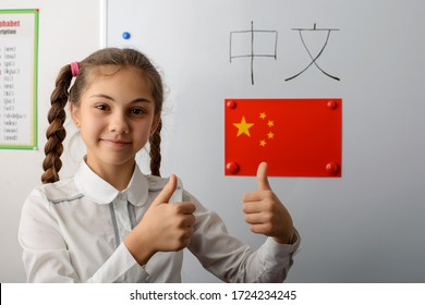 """Inscription """"Chinese"""" on chinese language on the whiteboard. Happy caucasian secondary school learner showing thumbs up. Concept of learning foreign language abroad"""