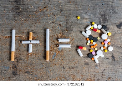 Inscription of cigarettes and a heap of pills on a wooden surface. Antismoking background