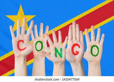 Inscription Congo on the children's hands against the background of a waving flag of the Congo