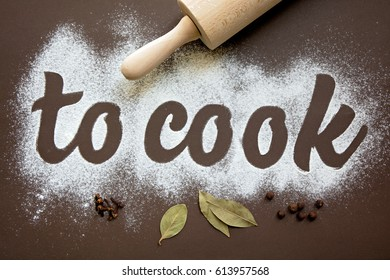 Inscription – to cook, written by flour. On the brown background.