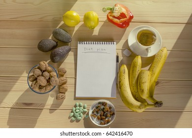 Inscription Diet Plan on empty notebook on wooden table with food around