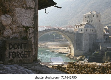 Inscription Don't forget on the Mostar bridge in Bosnia and Herzegovina in winter. People crossing the bridge. The Neretva river.