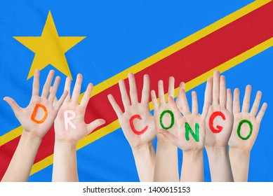 Inscription DR Congo on the children's hands against the background of a waving flag of the DR Congo