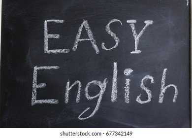 "The inscription ""Easy English"" is written chalk on the blackboard. English language learning. Getting education. Learning foreign languages."