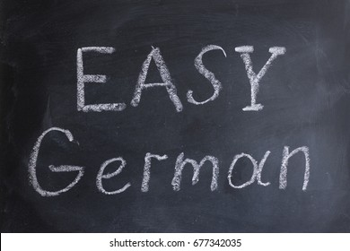 "The inscription ""Easy German"" is written chalk on the blackboard. German language learning. Getting education. Learning foreign languages."