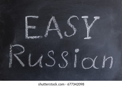 "The inscription ""Easy Russian"" is written chalk on the blackboard. Russian language learning. Getting education. Learning foreign languages."
