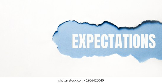 inscription Expectations word on blue torn papper.