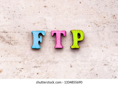 Inscription ftp File Transfer Protocol abbreviation in wooden letters on a light background.