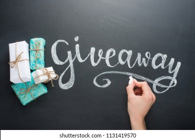 Inscription Giveaway written on the board with gifts