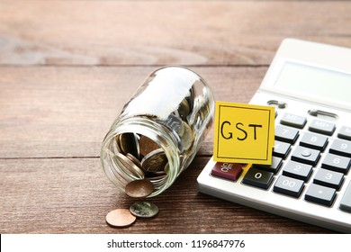 Inscription GST on paper with coins and calculator