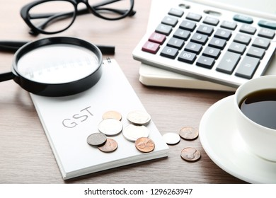 Inscription GST on paper with coins, magnifying glass, calculator and cup of coffee