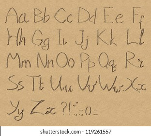 The inscription of handwritten alphabet letters and signs on wet beach sand background