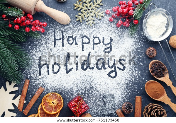 Inscription Happy Holidays on wheat flour background with fir-tree branches, orange fruits and cones