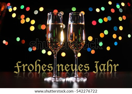 inscription happy new year in german language flutes of champagne in holiday setting