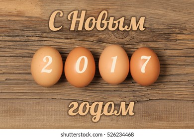 """Inscription """"Happy new year"""" in Russian language . Christmas eggs with the numbers 2017 on wooden board background."""