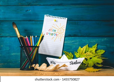 inscription in Hebrew Back to school on a sheet of paper with pencils and paper boat.