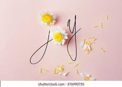 Inscription joy with white flowers on pink background