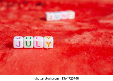 The inscription of the july  is made of cubes with letters lying on a watermelon