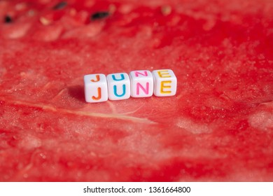 The inscription of the june is made of cubes with letters lying on a watermelon