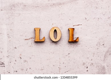 Inscription LOL LAUGHING OUT LOUD abbreviation in wooden letters on a light background.