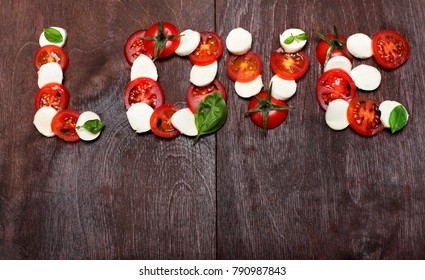 Inscription love of freshness mozzarella, raw tomatoes and basil.Ingredinet s of pizza.Against a dark wooden brown background. Creative valentine day background.Love concept.Spirit of Italy cuisine.