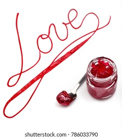Inscription love of red jam with jar with jam on the white background.Concept love.Valentine day.Food typography