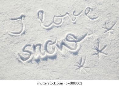 Inscription I love snow in the fresh snow in sunny winter day.