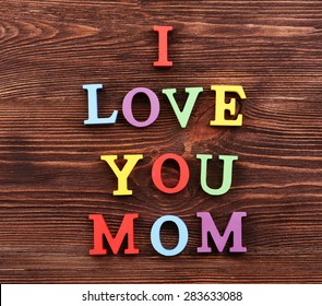 Inscription I LOVE YOU MOM made of colorful letters on wooden background