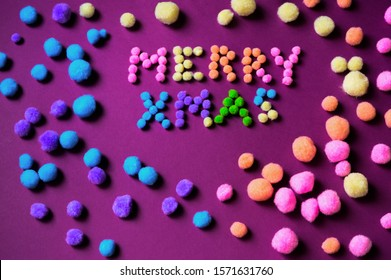 Inscription Merry Christmas assembled from small colorful polyester pompons on violet background with many pompons.