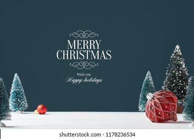 Сard with the inscription Merry Christmas. Bright red glass Christmas tree toy on a dark background with toy for Christmas tree in the background. A ball for decorating a Christmas tree
