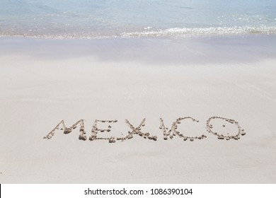 Inscription Mexico on the beach Letters on the sand. Summer concept of sandy beach. Space for text