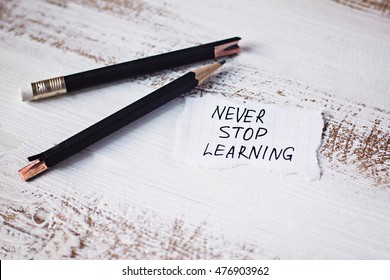 Inscription never stop learning on a piece of paper torn off with a broken pencil in half