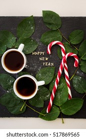 inscription of new year on a black board with sprigs of leaves and red candy - Shutterstock ID 517869565