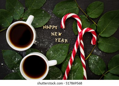 inscription of new year on a black board with sprigs of leaves and red candy - Shutterstock ID 517869568