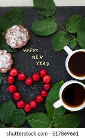 inscription of new year on a black board with cupcake and heart in the form of cherries - Shutterstock ID 517869661