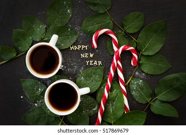 inscription of new year on a black board with sprigs of leaves and red candy - Shutterstock ID 517869679