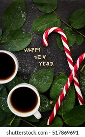 inscription of new year on a black board with sprigs of leaves and red candy - Shutterstock ID 517869691