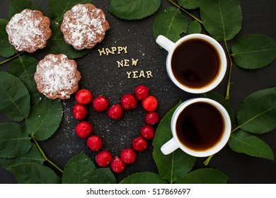 inscription of new year on a black board with cupcake and heart in the form of cherries - Shutterstock ID 517869697